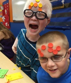 Ryan Abbott and Ethan Rieger with adhesive dots all over their faces.