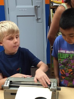 BELL student teaching Braille to a guest