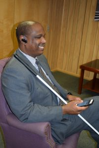 Blind person using iPhone with bluetooth earpiece while using NFB-NEWSLINE app