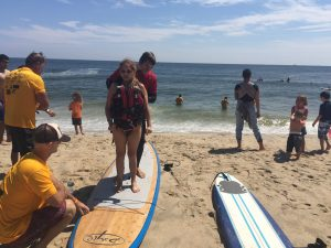 Rosa Santiago standing on surfboard at Surfing for Vision 2017